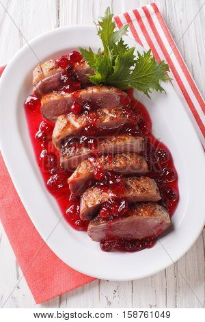 Tasty Sliced Roast Duck Breast With Cranberry Sauce On A Plate Close-up. Vertical Top View