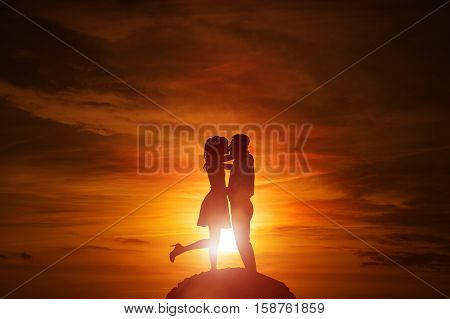 Silhouette of couple in love at the sunset with copy space