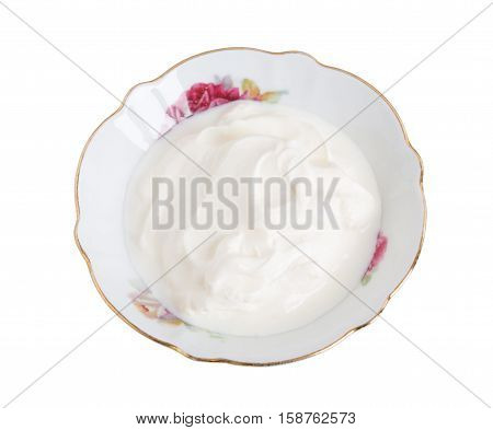 Fresh sour cream in bowl closeup. Isolated on a white background.