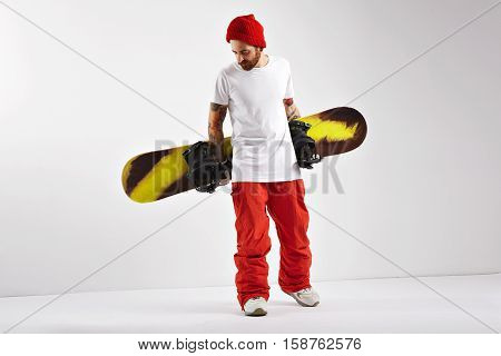 Fashionable bearded snowboarder in bright clothing and plain white cotton t-shirt holding his snowboard behind his back isolated on white