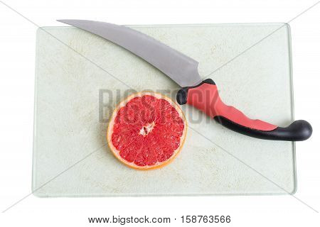 Sliced grapefruit and knife on platter. Isolated on a white background.
