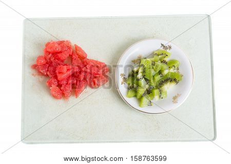 Minced grapefruit and kiwi on plastic platter. Isolated on a white background.