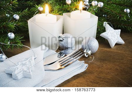 Table Place Setting for Christmas Eve. Winter Holydays. Christmas background. Cutlery on napkin candles and fir branches on rustic wooden background. Selective focus.