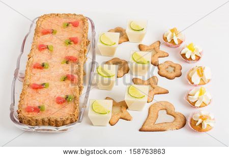Various delicious desserts on table. Located on a white background.