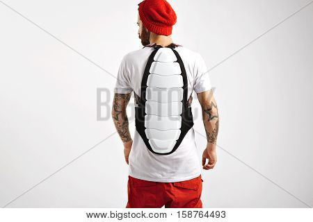 Snowboarding back protector worn by a muscular young tattooed snowboarder in red and white clothing in a studio with white walls