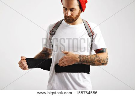 Serious young man fastening front straps of his snowboarding back protector over his plain white t-shirt against white wall background