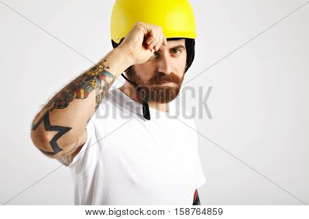 Serious tattooed and bearded young man looking into camera and adjusting his plain yellow snowboarding helmet isolated on white