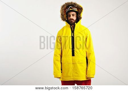 Casual shot of a young attractive bearded snowboarder presenting a bright yellow parka on white background