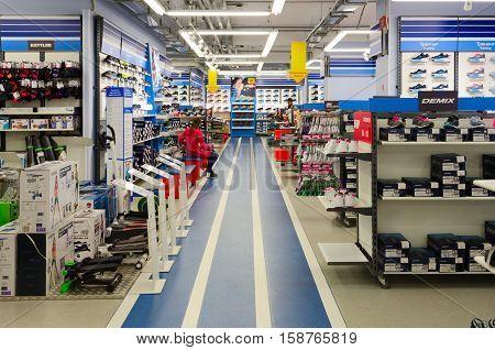 MOGILEV BELARUS - SEPTEMBER 28 2016: Unknown girl tries on sneakers in store of sporting goods