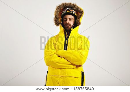 Attractive young man wearing snowboard helmet and goggles and a bright yellow anorak with arms crossed on white background