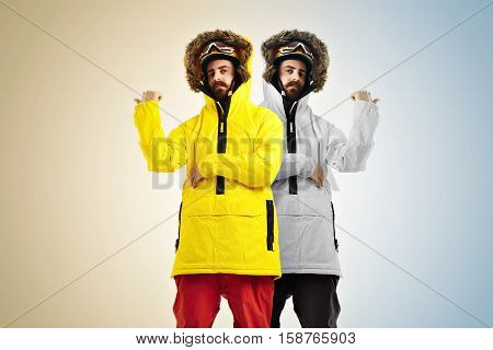 Two identical young men wearing snowboarding clothes in different hues - warm and cold - pointing out in opposite directions