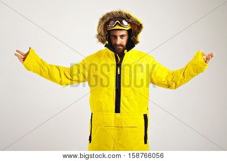 Portrait of a serious young snowboarder in bright anorak coat outstretching his arms and looking into camera isolated on white