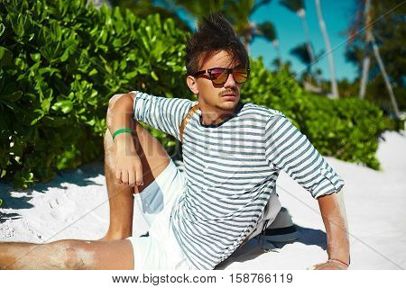 Stylish young male model man lying on beach sand wearing hipster summer hat enjoying summer travel holiday near ocean in sunglasses