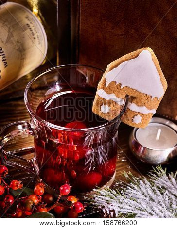 Hot alcohol punch with ginger pastry in form of house decorated punch mug. Red berry and candles near punch mug.