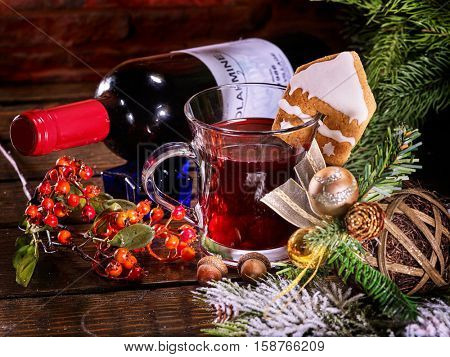 Still life of lying on snow-covered fir branches red wine bottle and mug with Christmas hot mulled wine. Label on bottle. Gingerbread cookie in form of house on mug. Christmas ball and Christmas tree.