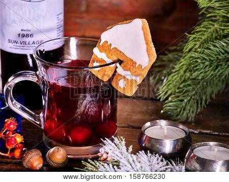 Still life of warming drink with bottle of red wine . Label on bottle of wine. Warming mulled wine with cookie in form of house on brick wall.