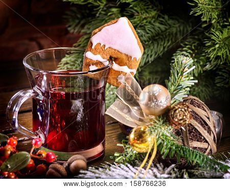 Christmas still life with hot drink. Warming mulled wine with cookie in form of house and Christmas ball on spruce branch. Traditional drink during winter especially around Christmas.