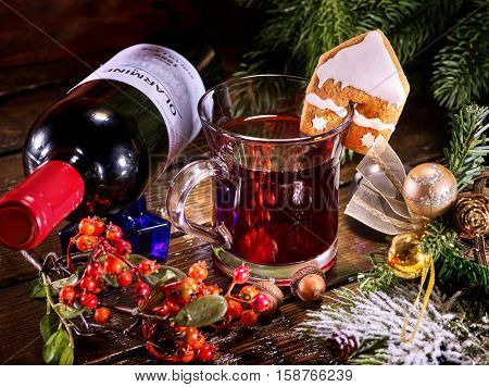 Still life of lying on table red wine bottle and mug with Christmas hot mulled wine. Label on bottle. Gingerbread cookie in form of house on mug. Christmas ball and Christmas tree.