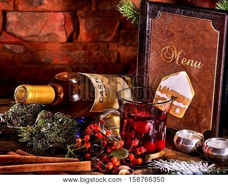 Warming grog with bottle of white wine . Label on bottle of wine. Bottle lying on winter berry. Ginger snap in form of house decorated grog mug. Brick wall and card menu background.