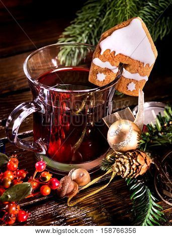 Christmas still life with hot drink. Warming mulled wine with cookie in form of house and Christmas ball on spruce branch.
