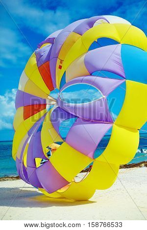 bright colorful Rainbow Parachute on the beach behind blue ocean water