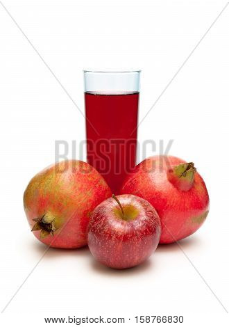 pomegranate red apple and a glass of juice on a white background. vertical photo.