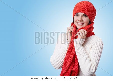 A portrait of hazel-eyed beautiful woman with pleasant smile wearing red hat with scarf and white warm knitted sweater holding her hands on her scarf. Dreams about New Year and winter holidays.
