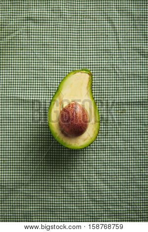 Top shot of a halved avocado on a table covered with green and white gingham tablecloth