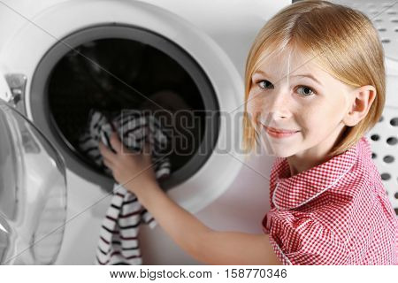 Small girl putting cloth into washing machine