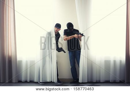 Male thieves with gun behind curtains