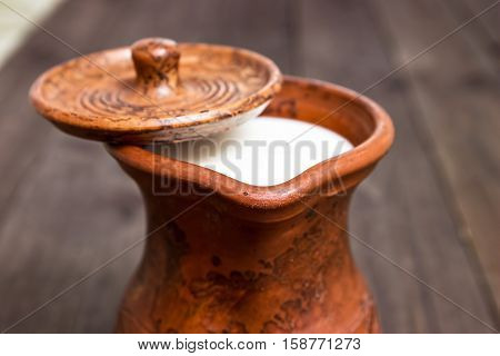 Milk in a clay jug. Bio products. Food background.