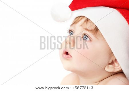 Closeup portrait of a cute little baby boy wearing red Santa Claus hat isolated on white background, traditional Christmas costume
