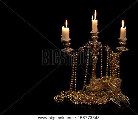 Vintage candlestick with burning candles and Christmas Golden ornaments on black background.