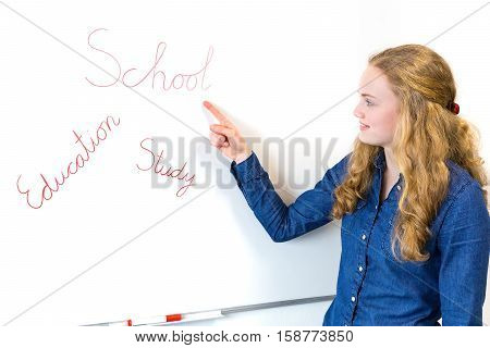 School girl pointing at education words on whiteboard