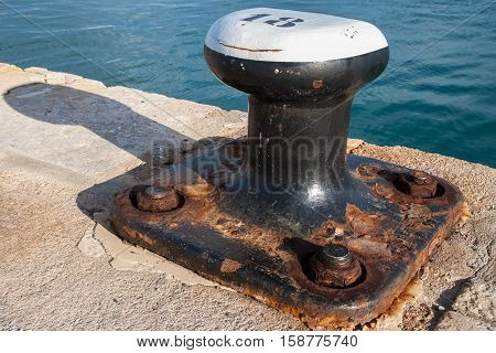 A cast iron mooring bollard showing rust and oxidation