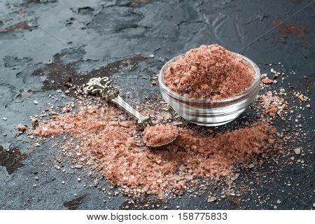Special pink Adygei salt with spices (Russia) in a glass salt shaker and spoon on a dark textured background. Prepared according to the old recipe with garlic and spices. Useful economically spent