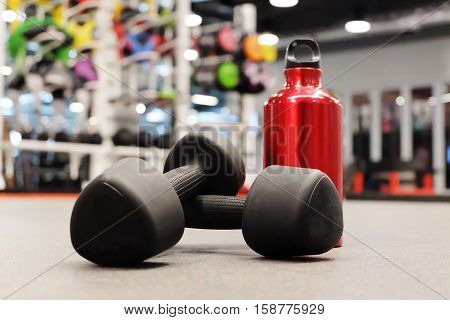 Sports Equipment Dumbbells And Bottle Of Red Water In Sport Club Or Gym And Fitness Room.
