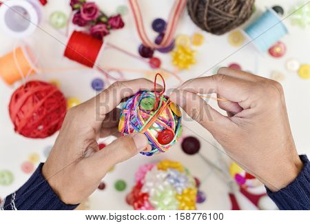 closeup of a young man making a handmade christmas ball with strings and buttons of different colors, and a pile of different haberdashery items on a white surface