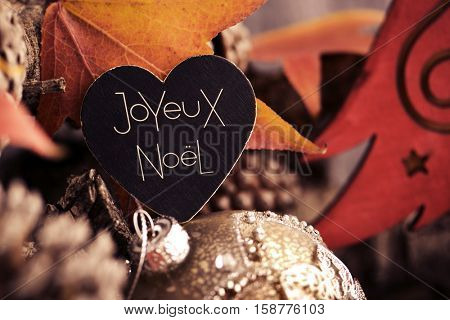 the text joyeux noel, merry christmas written in french in a heart-shaped signboard and some pine cones and christmas balls