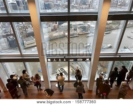 LONDON - NOVEMBER 27: Tourists sightseeing the River Thames and City of London from the observation gallery on the 69th floor of The Shard on November 27, 2016 in London, UK.