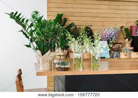 Small business. Modern flower shop interior elements. Floral design studio, sale of decorations and arrangements. Flowers delivery service and sale of home plants in pots, wooden showcase.