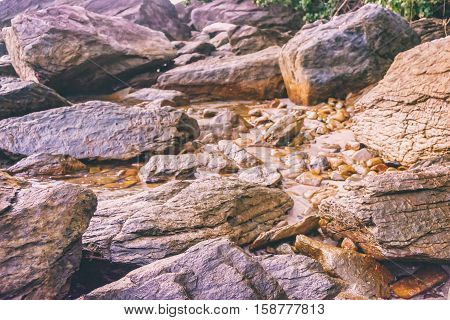 Rocky shore texture background. Stones Rocks Sand on sunset time. Selective focus