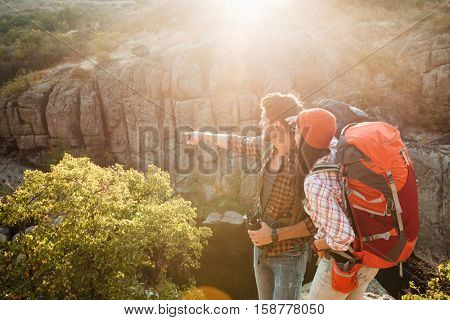 Adventure couple stands sideways near the canyon. man shows away