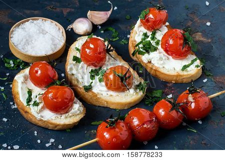 Crostini with toasted baguette cottage cheese and grilled cherry tomatoes on an old blue textured background. Tomatoes cooked with olive oil garlic salt and pepper