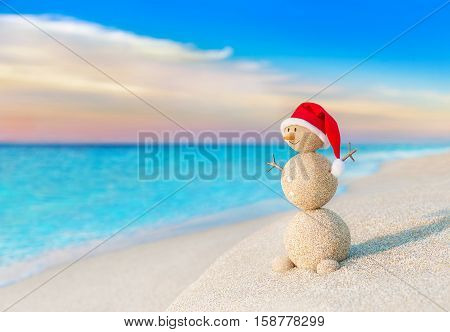 Christmas positive Sandy Snowman in red Santa Claus hat at ocean sunset beach. New Year vacation discounts in hot countries destinations concept