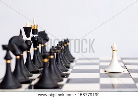 chess white pawn in front of black pieces