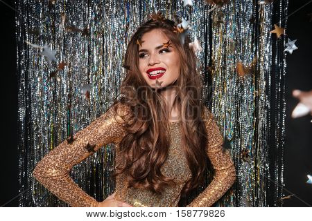 Happy beautiful young woman in evening dress standing over star shaped confetti on shining background