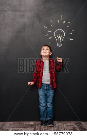 Image of little cute boy having an idea over chalkboard background with drawings. Looking up to drawings.