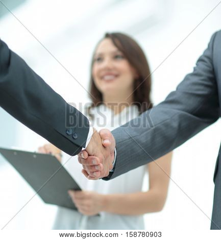 handshake of two businessmen in the background assistants with d
