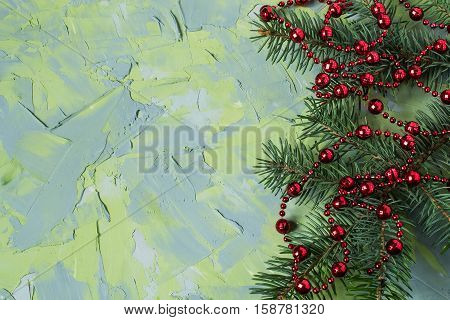 Festive Christmas background with fir branches and beads on the textured surface of the blue and green putty. Empty space for text